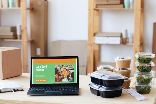 Ноутбук с веб-сайтом службы доставки еды и коробками с едой на столе в офисе