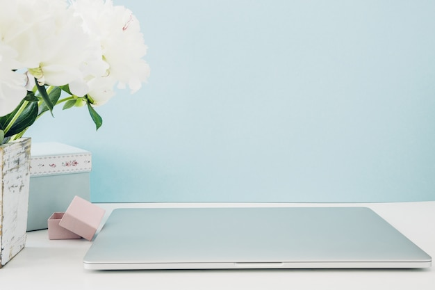 白い空白の画面と青のテーブルの上に花瓶に花とノートパソコン。モックアップ