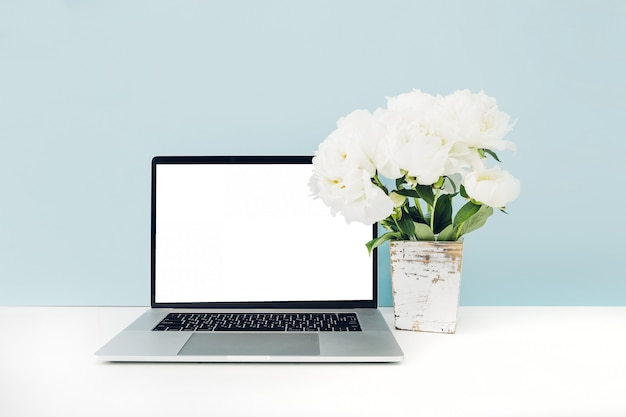 Laptop with white blank screen and flowers in vase on table on blue. mock up
