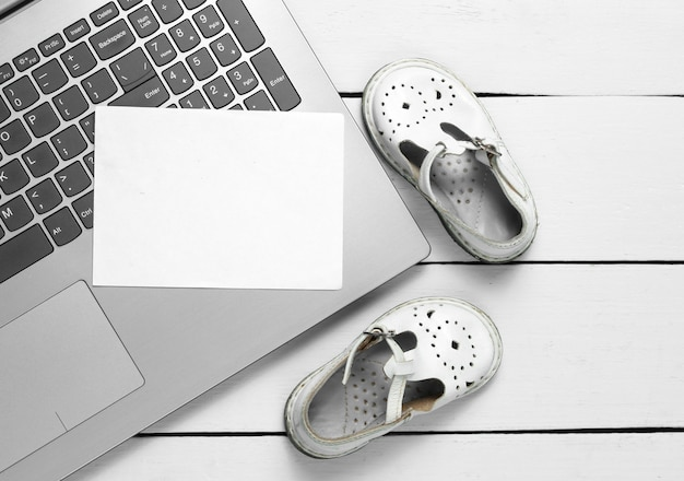 Laptop with white piece of paper for copy space and kids sandals on wooden