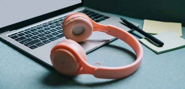 白い画面とピンクのヘッドフォンが横にあるノートパソコン