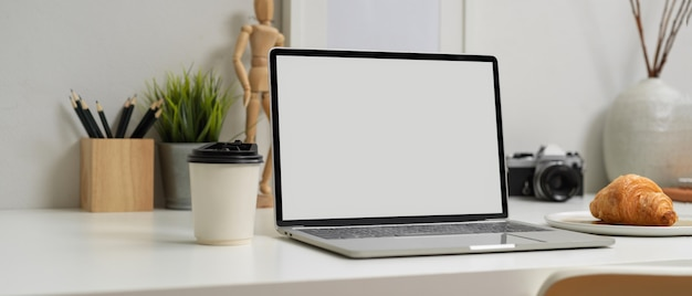 Laptop with white screen and a croissant