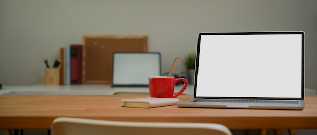 Laptop with white screen and a mug