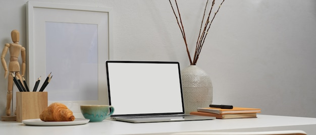 Laptop with white screen and a notebook
