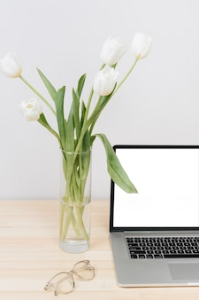 Laptop with white tulips in vase on table