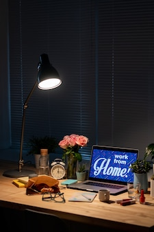 Laptop with work from home notice on display, copybook, snack and drink, flowers and alarm clock with lamp over the supplies in dark room