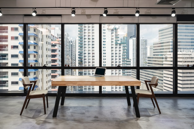 Laptop on wooden conference table with chair social distancing concept in reopen modern office