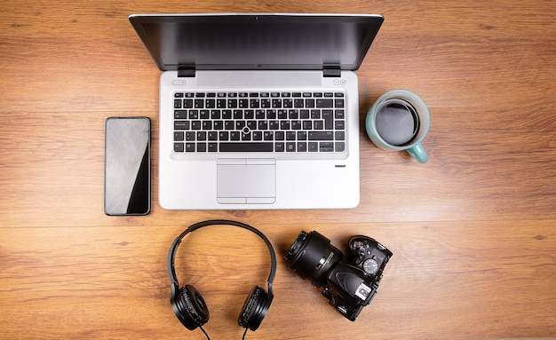 Laptop on wooden desk with a cup of coffee headphones a dslr camera and a celular phone smartphone