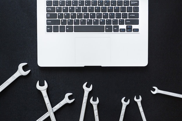 Laptop and wrench on black background, top view, flat lay