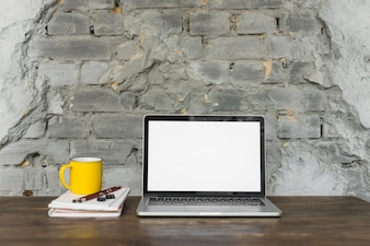 Laptop; yellow cup; and stationeries on wooden table