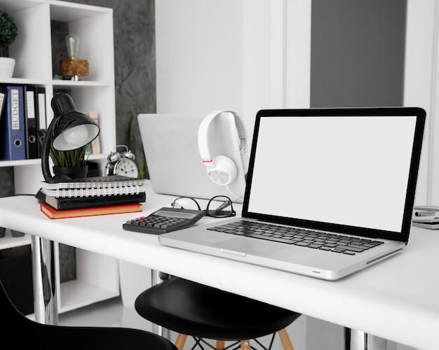 ノートブックとオフィスデスク上の電卓を備えたラップトップ