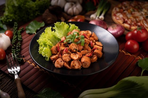 Колбаса ларб с зеленым луком чили и листьями салата в черной тарелке