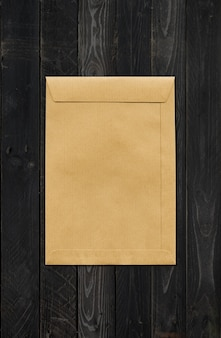 Large a4 brown paper enveloppe mockup template isolated on black wood background