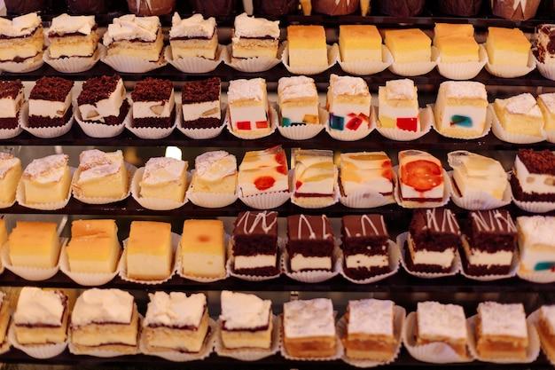 豊富な種類のデザートがショーケースに展示されています。ホテルの甘いテーブル。小売ショーケース。休息と楽しみ。お祝いのイベント。
