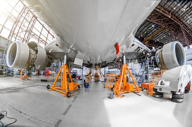 A large aircraft for service maintenance on special jacks in the hangar.