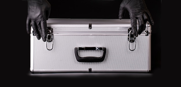 The large aluminum suitcase and hands black safety gloves