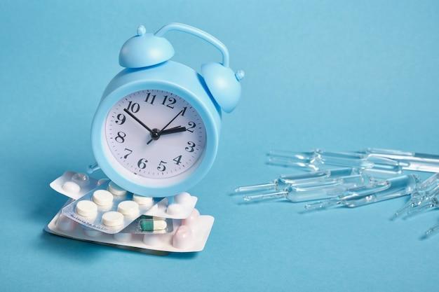 大きなアンプル、青い背景にさまざまな錠剤のパッケージの山に水色の目覚まし時計、コピースペース、時間の概念に薬を服用