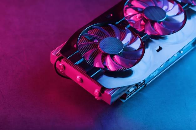 Большая и мощная видеокарта с тремя вентиляторами с сине-розовой подсветкой. концепция видеочипа cyberpunk для игр и майнинга криптовалюты. темный ключ, вид сверху