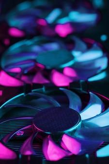 Большая и мощная видеокарта с тремя вентиляторами с сине-розовой подсветкой.