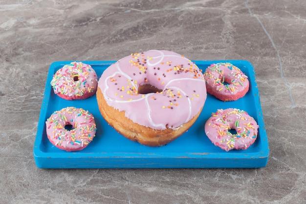 Большие и маленькие пончики, расположенные на синем блюде на мраморной поверхности