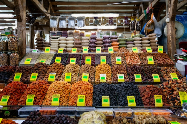 A large assortment of nuts and dried fruits on the counter in the market. front view. healthy nutrition and vegetarianism.