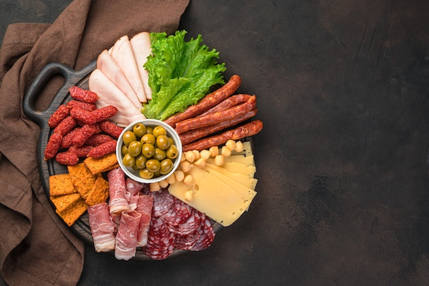 Large assortment of sausage and cheese on a round board on a brown desk. top view.