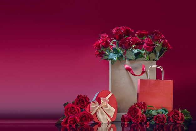 A large bag filled with red roses heart shaped gift box roses beads on a mirror surface