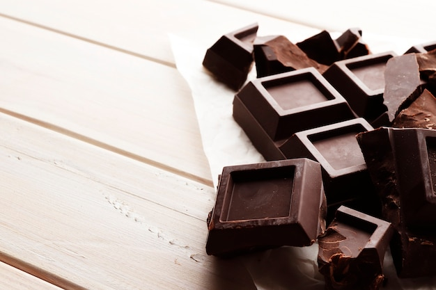 A large bar of black chocolate on a white wooden background with space for text.