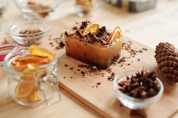 Большой батончик с палочками корицы, звездчатым анисом и дольками апельсина, а также стеклянная посуда с другими принадлежностями для изготовления мыла ручной работы