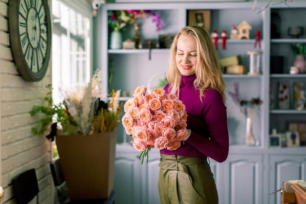 여자 손에 혼합 된 꽃의 큰 아름 다운 꽃다발. 꽃 가게 개념. 잘 생긴 신선한 꽃다발. 꽃 배달.