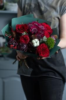 여자 손에 혼합된 꽃의 큰 아름다운 꽃다발. 꽃 가게 개념입니다. 잘생긴 신선한 꽃다발입니다. 꽃배달.