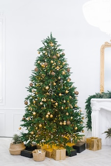 Large beautiful christmas tree decorated with beautiful shiny trinkets and lots of different gifts on the floor.