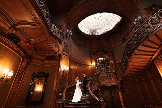 Large beautiful hall decorated with wooden carving. newlyweds hold hands on chic wooden stairs.