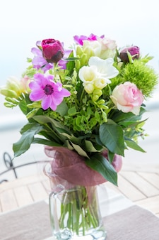 나무 탁자 위의 꽃병에 있는 모란, 장미, 아네모네, 흰색 프리지아의 크고 아름다운 분홍색 꽃다발. 봄 꽃 개념입니다.