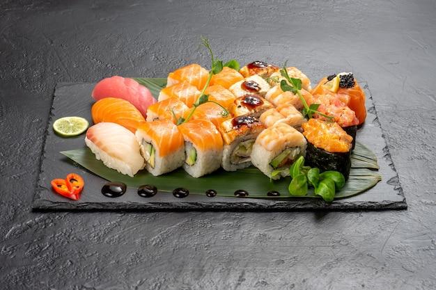 Large beautiful set of different types of sushi maki and nigiri on a black rectangular stone slate plate