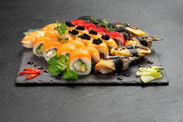 Large beautiful set of different types of sushi maki and nigiri on a black rectangular stone slate plate.