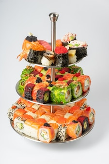 A large beautiful set of different types of sushi maki, nigiri and gunkans on a three-tiered plate