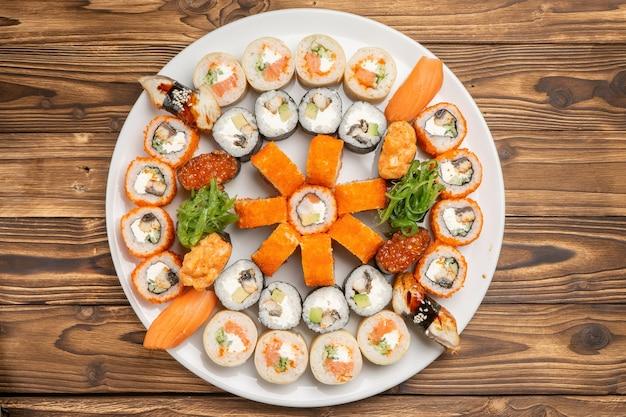 A large beautiful sushi set with maki rolls, nigiri and gunkans on a white round ceramic plate