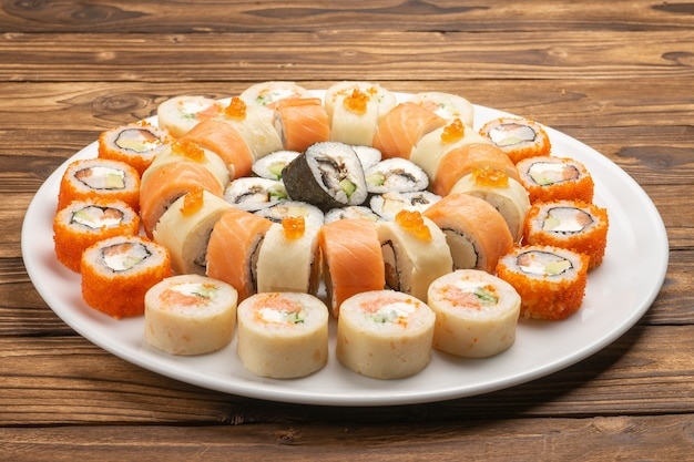 Large beautiful sushi set with maki rolls of salmon, eel, nori, rice, red caviar and avocado on a white round ceramic plate