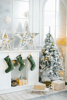 A large beautifully decorated christmas tree stands in the room next to the fireplace.