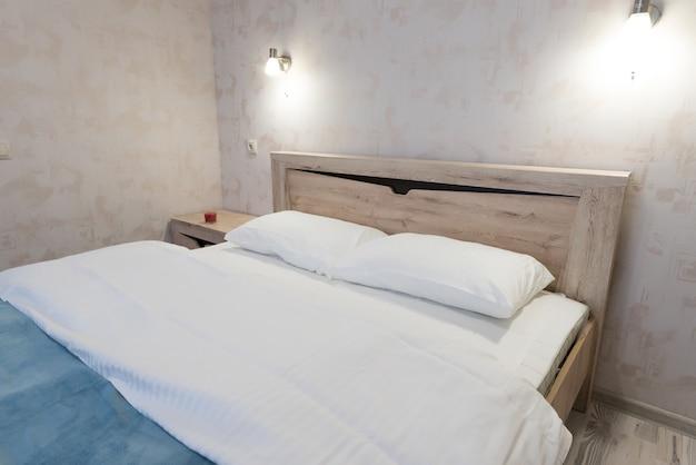 산뜻한 흰색 린넨과 베개가 있는 대형 침대