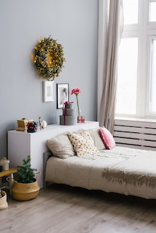 Large bed with pillows in the bedroom, decorated for christmas and new year