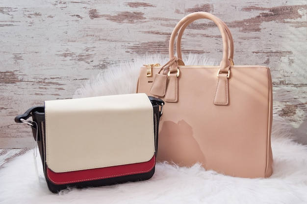 Large beige and white-red bags on a white artificial fur. fashionable concept