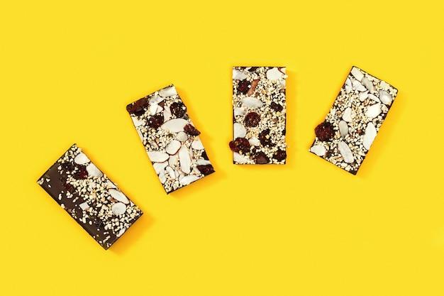 Большая надкушенная плитка шоколада с орехами и сухофруктами, разбита на четыре части на желтом