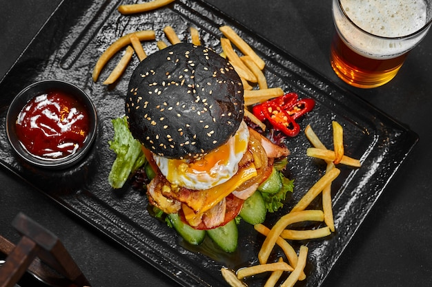 野菜チキンキャラメリゼオニオン目玉焼きとベーコンと大きな黒いチーズバーガー