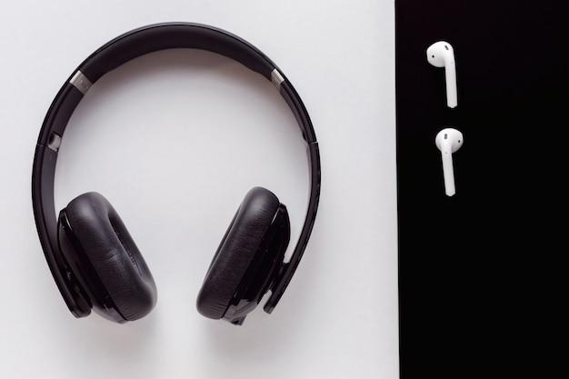 Большие черные наушники на белом фоне, маленькие белые наушники на черном фоне вид сверху с копией пространства для текста