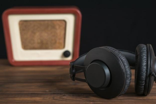 복고풍 라디오의 배경에 큰 검은색 헤드폰. 사운드 및 비디오 재생 기술.
