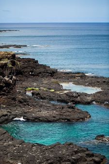 Большие черные камни на берегу индийского океана. маврикий.
