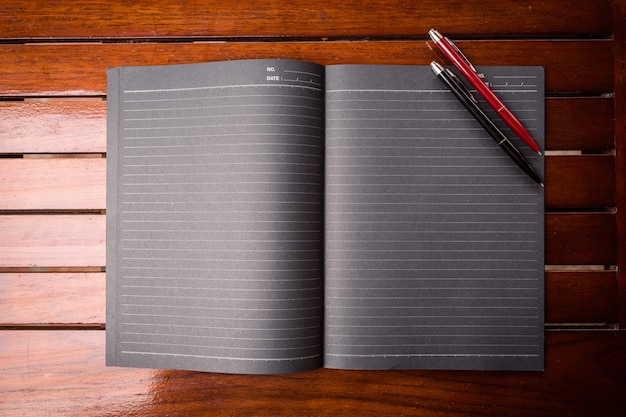 A large black writing pad on which are two office pens in black and red located on a wooden table