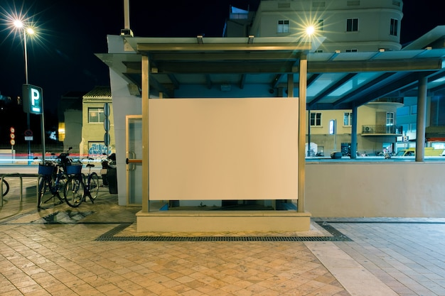Large blank billboard on a street wall at night